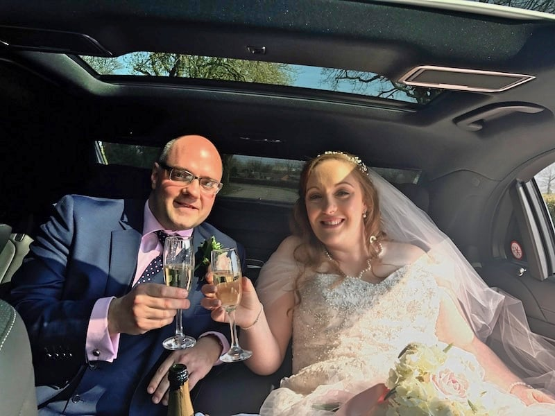 Raising a glass of Champagne on the back of the Mercedes S Class Wedding Car Derby