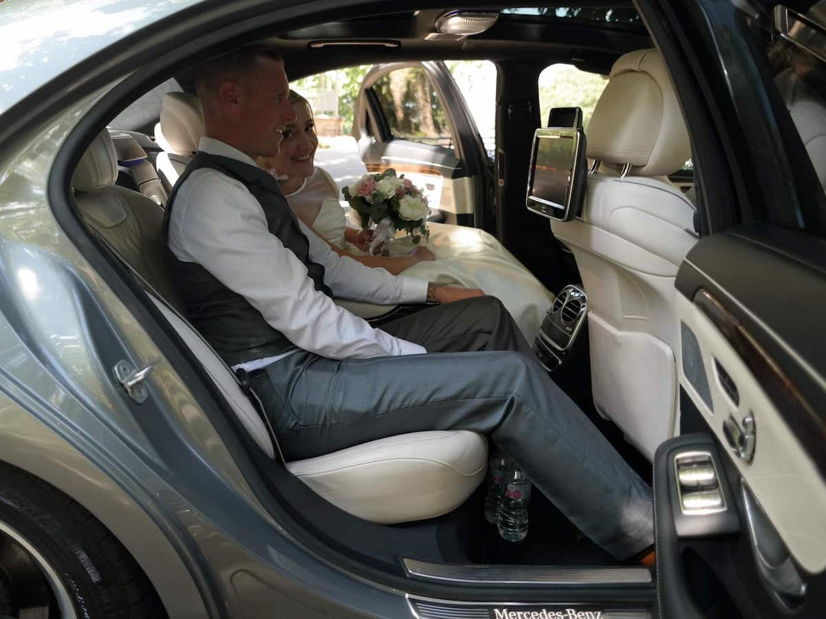 Bride and groom sat in the Mercedes S Class wedding car